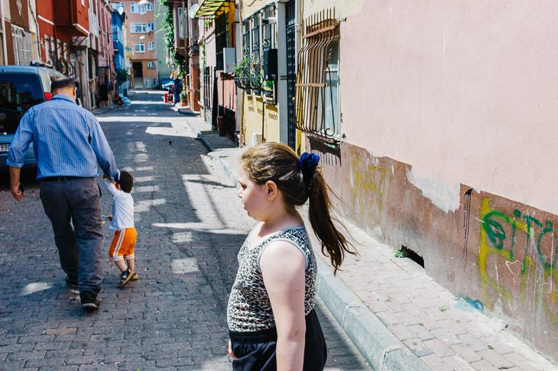 Девочка в центре кадра стоит боком. Справа пустая стена. Слева мужчина почти слился по тону с машиной. Никакой композиции.